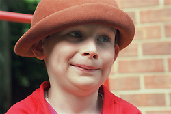 Portrait of young boy with autism wearing felt hat,
