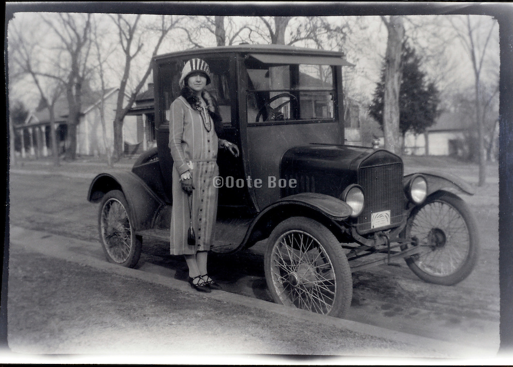 fashionable dressed woman standing by car USA 1920s