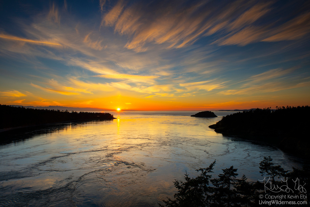 Wispy cirrus clouds take on the golden color of the sun as it sets over Deception Pass in Island County, Washington. Deception Pass is a strait that connects the Strait of Juan de Fuca with Skagit Bay, separating Whidbey (left) and Fidalgo (right) islands.