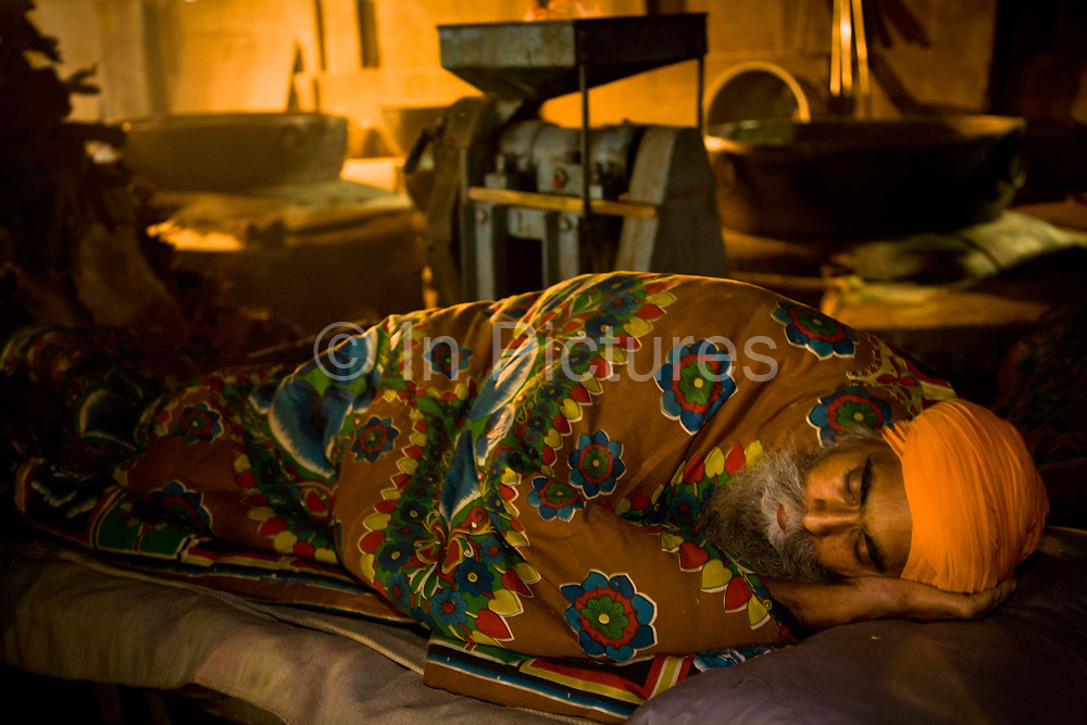 A Sikh man goes to sleep after a day's work inside the Golden Temple's Langar, Amritsar, Punjab, India