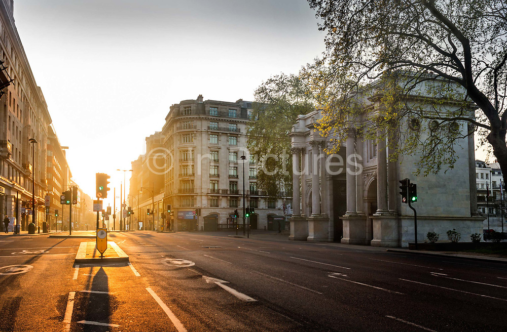 Early morning looking East along Oxford Street from Marble Arch, on 16th April 2020 in London, United Kingdom. Normally crowded with people, London is like a ghost town as workers stay home under lockdown during the Coronavirus pandemic. Marble Arch is a 19th-century white marble-faced triumphal arch in London, England. The structure, based on that of the Arch of Constantine in Rome, was designed by John Nash in 1827 to be the state entrance to the cour dhonneur of Buckingham Palace. In 1851, on the initiative of architect and urban planner Decimus Burton, a one-time pupil of John Nash, it was relocated and following the widening of Park Lane in the early 1960s to where it is now sited, incongruently isolated, on a large traffic island at the junction of Oxford Street, Park Lane and Edgware Road.