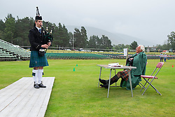 Piper and judge at Solo piping competition at Braemar Junior Highland Games in July in Scotland United Kingdom
