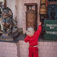 A youngster spins a prayer wheel at Swayambu Temple in Kathmandu, Nepal, 1986.