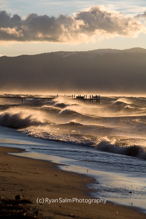 High winds and morning clouds create a beautiful sunrise on Lake Tahoe.