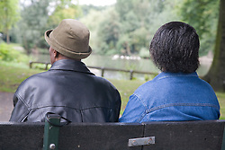 Older couple sitting down in the park together,