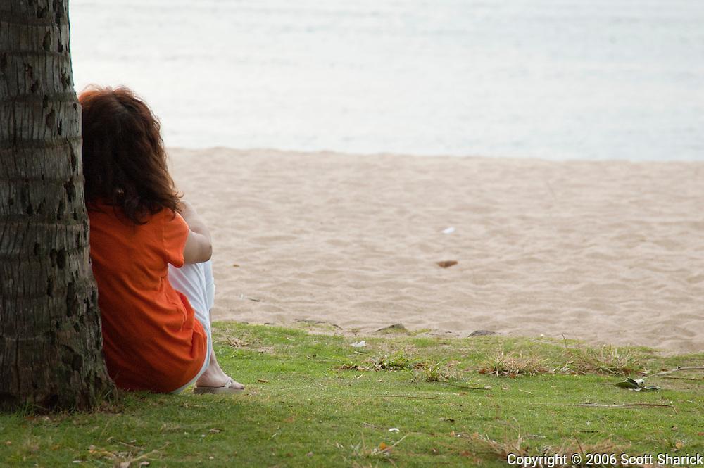 A lone woman sits on Waikiki beach thinking.