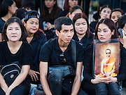 15 OCTOBER 2016 - BANGKOK, THAILAND:  People mourning the death of Bhumibol Adulyadej, the King of Thailand, sit on the sidewalk in front of the Grand Palace in Bangkok. King Bhumibol Adulyadej died Oct. 13, 2016. He was 88. His death comes after a period of failing health. With the king's death, the world's longest-reigning monarch is Queen Elizabeth II, who ascended to the British throne in 1952. Bhumibol Adulyadej, was born in Cambridge, MA, on 5 December 1927. He was the ninth monarch of Thailand from the Chakri Dynasty and is known as Rama IX. He became King on June 9, 1946 and served as King of Thailand for 70 years, 126 days. He was, at the time of his death, the world's longest-serving head of state and the longest-reigning monarch in Thai history.     PHOTO BY JACK KURTZ