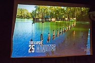 """Merrick, New York, USA. 11th June 2017.  During """"American Grit"""" Season 2 premiere, (6th from far right) CHRIS EDOM, 48, of Merrick, is one of 17 contestants suspended from beams above lake water during an endurance challenge. """"TIME ELAPSED: 25 MINUTES"""" is superimposed on scene. Show was projected on large screen during Edom's backyard Viewing Party for Episode 1 of FOX network reality television series."""
