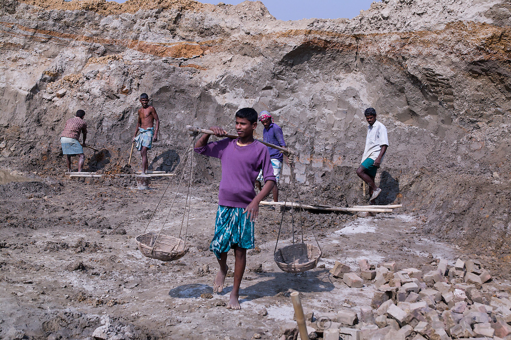 Men digging from piles of earth for mud for the bricks, Bangladesh.