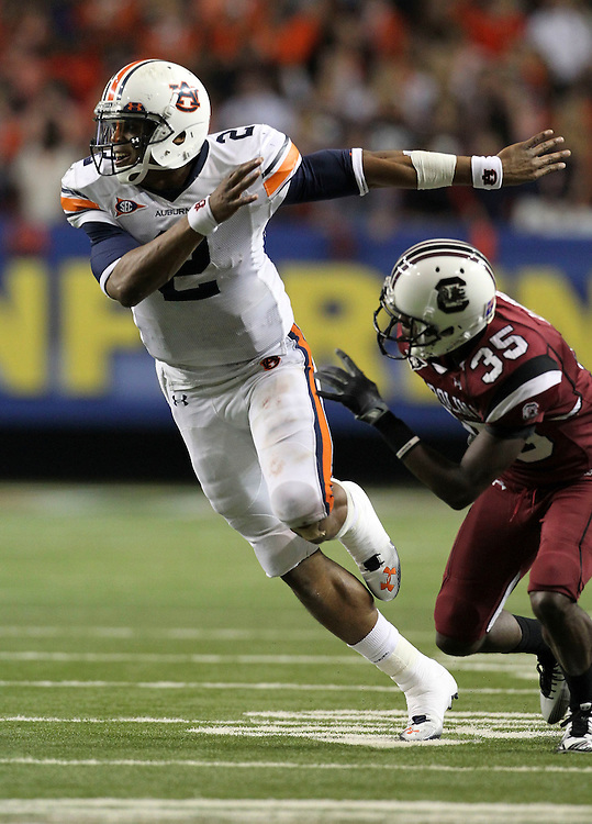 ATLANTA - DECEMBER 04:  Quarterback Cam Newton #2 of the Auburn Tigers goes out for a pass as a wide receiver while cornerback Jimmy Legree #35 of the South Carolina Gamecocks covers him during the 2010 SEC Championship at Georgia Dome on December 4, 2010 in Atlanta, Georgia.  The Tigers beat the Gamecocks 56-17.  (Photo by Mike Zarrilli/Getty Images)