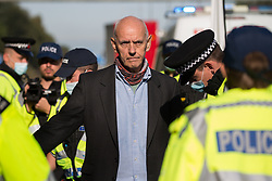 Ockham, UK. 21st September, 2021. An Insulate Britain climate activist is arrested by Surrey Police after blocking the clockwise carriageway of the M25 between Junctions 9 and 10 as part of a campaign intended to push the UK government to make significant legislative change to start lowering emissions. Both carriageways were briefly blocked before being cleared by Surrey Police. The activists are demanding that the government immediately promises both to fully fund and ensure the insulation of all social housing in Britain by 2025 and to produce within four months a legally binding national plan to fully fund and ensure the full low-energy and low-carbon whole-house retrofit, with no externalised costs, of all homes in Britain by 2030.
