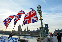 © Licensed to London News Pictures. 07/02/2020. LONDON, UK.  Union Jack flags flutter in the wind at a souvenir stall on Westminster Bridge opposite the Houses of Parliament.  A week has passed since the UK left the European Union with 11 month's worth of negotiations to be undertaken to formalise trade deals.  Photo credit: Stephen Chung/LNP