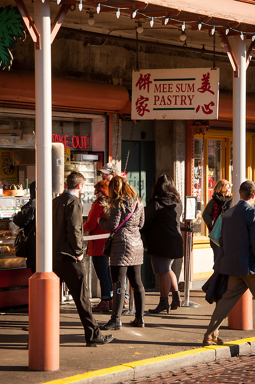 2017 DECEMBER 05 - People walk past Mee Sum Pastry at Pike Place Market, Seattle, WA, USA. By Richard Walker