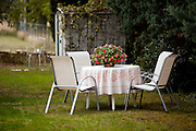 A table is set in the garden of a family living in  L'Isle-sur-la-Sorgue, France
