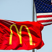 The flag of the giant fast food chain Mcdonald's flies in the breeze next to an American flag.