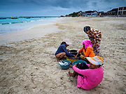 03 AUGUST 2017 - KUTA, BALI, INDONESIA: Women sell fish caught overnight by villagers who live along Jimbrana Beach in Kuta. The beach is close to the airport and a short drive from other beaches in southeast Bali. Jimbrana was originally a fishing village with a busy local market. About 25 years ago, developers started building restaurants and hotels along the beach and land prices are rising. The new emphasis on tourism is changing the nature of the area but the fishermen are still busy very early in the morning.    PHOTO BY JACK KURTZ