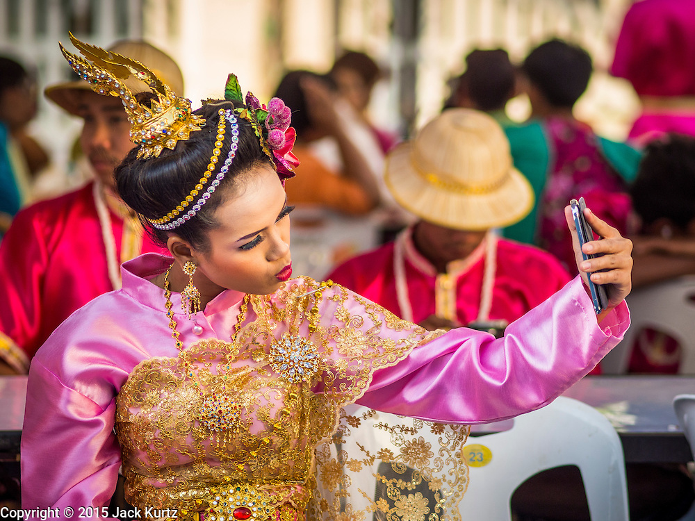 """14 JANUARY 2015 - BANGKOK, THAILAND: A girl in traditional attire snaps a """"selfie"""" before the 2015 Discover Thainess parade. The Tourism Authority of Thailand (TAT) sponsored the opening ceremony of the """"2015 Discover Thainess"""" Campaign with a 3.5-kilometre parade through central Bangkok. The parade featured cultural shows from several parts of Thailand. Part of the """"2015 Discover Thainess"""" campaign is a showcase of Thailand's culture and natural heritage and is divided into five categories that match the major regions of Thailand – Central Region, North, Northeast, East and South.     PHOTO BY JACK KURTZ"""