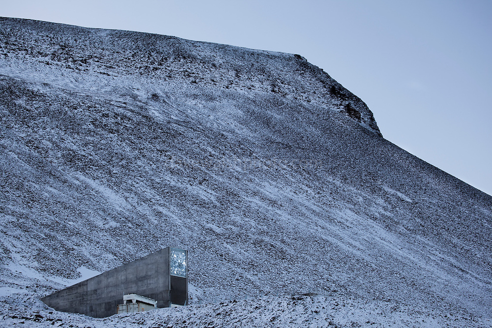 "Nestled into the rocky waste of plataberget Mountain about Svalbard's airport, the Global Seed Vault is at once startling and innocuous. Designed by architect Peter W. Søderman at Barlindhaug Consulting, this concrete, steel and glass structure is the first layer of security to a repository of millions of seeds from around the world, stored here in case of disaster, disease, or war...The Svalbard Global Seed Bank is situated 120 metres (390 ft) inside a sandstone.mountain at Longyearbyen on Spitsbergen Island, in the Svalbard archipelago about 1300km from the North Pole. Svalbard was considered ideal for the bank, due to low tectonic activity and its permafrost, which will aid preservation. Even if sea levels rise due to climate change - and the melting of ice caps, the seeds will be safe and dry , as they are stored at a location 130 metres (430 ft) above sea level. ..The Svalbard Global Seed Vault  provides a safety net against accidental loss of diversity from traditional storage within genebanks around the world, and has a capacity for 4.5 million seeds. Although the media has made much of the ""Doomsday Vault's"" role in providing security in the face of war or or catastrophe, the operators - the Norwegian government  and the Global Crop Diversity Trust and the Nordic Genetic Resource Center - say that it will be most useful when genebanks lose samples due to mismanagement, accident, equipment failures, funding cuts and natural disasters. This mage can be licensed via Millennium Images. Contact me for more details, or email mail@milim.com For prints, contact me, or click ""add to cart"" to some standard print options."