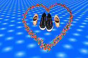 Heart shape formed from sweets with two pairs of shoes within
