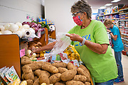 "08 JULY 2020 - JEWELL, IOWA: DIANE BARKEMA, from Jewell, shops at the Jewell Market on the day the store reopened. Barkema said before the store reopened she had to drive more than 20 miles to go to a grocery store, but that since the start of the COVID-19 pandemic she hadn't done any in store shopping, buying all of her groceries on line. She said she was happy to have the store open because it meant she could shop locally. Her trip to the Jewell Market was her first time in a grocery store since the middle of March. The only grocery store in Jewell, a small community in central Iowa, closed in 2019. It served four communities within a 20 mile radius of Jewell. Some of the town's residents created a cooperative to reopen the store. They sold shares to the co-op and  held fundraisers through the spring. Organizers raised about $225,000 and bought the store, which reopened July 8. Before the reopening, Jewell had been a ""food desert"" for seven months. The USDA defines rural food deserts as having at least 500 people in a census tract living 10 miles from a large grocery store or supermarket. There is a convenience store in Jewell, but it sells mostly heavily processed, unhealthy snack foods that are high in fat, sugar, and salt.         PHOTO BY JACK KURTZ"