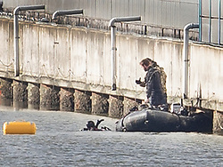 © Licensed to London News Pictures. 12/02/2018. London, UK. Members of the Royal Navy Bomb Disposal Team watch from a boat as one of their colleagues surfaces (L) after diving at the location of the unexploded bomb next to London City Airport which remains closed. A World War II era bomb was found in The River Thames during routine work on nearby King V Dock. Police have evacuated nearby residents, closed the airport and set up a 214-metre exclusion zone. Photo credit: Peter Macdiarmid/LNP