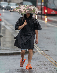 © Licensed to London News Pictures. 28/04/2020. London, UK. A man with protective covers on his shoes in Parliament Square, Westminster as members of the public go to work during lockdown as heavy rain hits London after the warm sunny weather over the weekend. Today temperatures are expected to only reach 10c. London has also seen an increase in traffic and busier High Streets as more shops and cafes start to open up during the coronavirus pandemic crisis. Photo credit: Alex Lentati/LNP