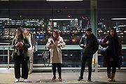 Commuters waiting for trains. London overland railway system and underground trains.