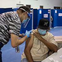 RN Ernesto Gonzalez administers the Pfizer COVID-19  vaccine to Leo Kimlicheeney in the gymnasium on the University of New Mexico Gallup campus during Gallup Indian Medical Center's COVID-19 vaccination event Saturday morning.