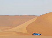 Car parked next to a huge sand dune in the Namib Desert near Swakopmund. The area is famous and very popular for sandboarding. Namibia
