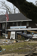 Residents of  Bay St. Louis Mississippi hand a sign  outside their home after hurricane katrina destroyed downtown olde town in bay st. louis.sludge in their neighbor while walking their dog past what used to be St. Augustines Retreat.Tuesday August 31,2005. Waveland was in Hancock county and was one of the hardest hit communities.Hurricane Katrina is the worst natural disaster to hit ame