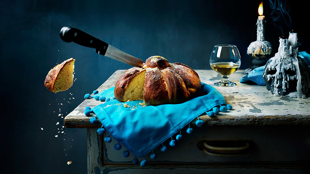 Pan de Muerto - Day of The Dead. Piece of the traditional Mexican bread floating in mid air.