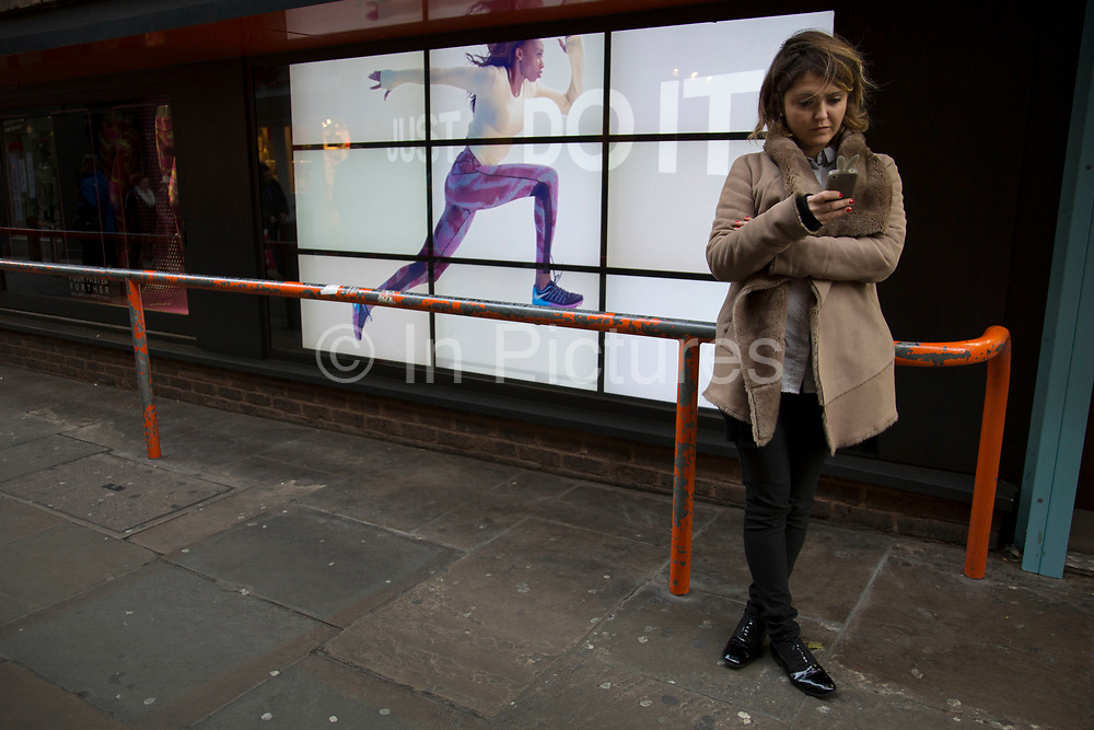 """Nike advertising runner runs along a barrier near unsuspecting people. The video advert with the slogan 'Just Do It"""" with a woman running across the screen makes for an optical illusion of sorts and a strange urban scene. London, UK."""
