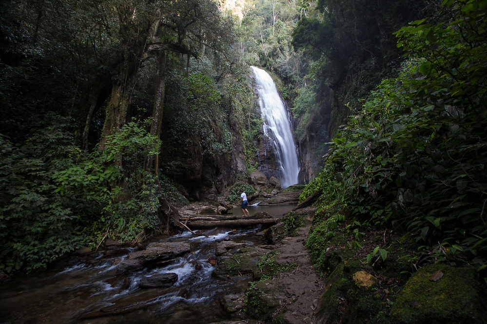 The Meu Deus waterfall in the Sapatú quilombo, São Paulo state, Brazil.<br /> <br /> Debora walks across a makeshift bridge, she is an activist in the Movement of People Affected by Dams (Movimento dos Atingidos por Barragens, MAB) who are in active resistance against new dams in the region, to protect water resources like this.<br /> <br /> Quilombos are remote hinterland settlements in Brazil set up by escaped slaves of African origin. Though most of them were destroyed by slave owners and the Brazilian state, today there are around 5,000 recognised quilombos in Brazil. Slavery was legal in Brazil for four centuries and some five million slaves were brought to Brazil, most of them from the Angola area. <br /> <br /> While the world is slowly agreeing with the scientific community on man's contribution to climate change through emissions, the implementation of large-scale hydroelectric projects has massive impacts on water resources, and the indigenous and quilombo communities that depend on them.