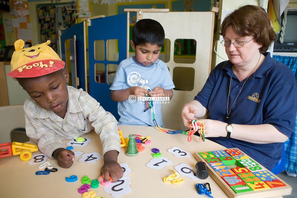 Nursery nurse helping children with numeracy skills,