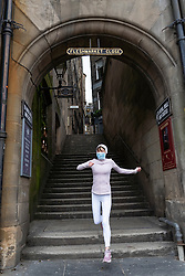 Edinburgh, Scotland, UK. 29 April 2020. Views of Edinburgh Old Town as coronavirus lockdown continues in Scotland. Streets remain deserted and shops and restaurants closed and many boarded up. Scottish Government now recommends public to wear face masks. Female jogger wearing face mask runs out of an empty Fleshmarket Close. Iain Masterton/Alamy Live News