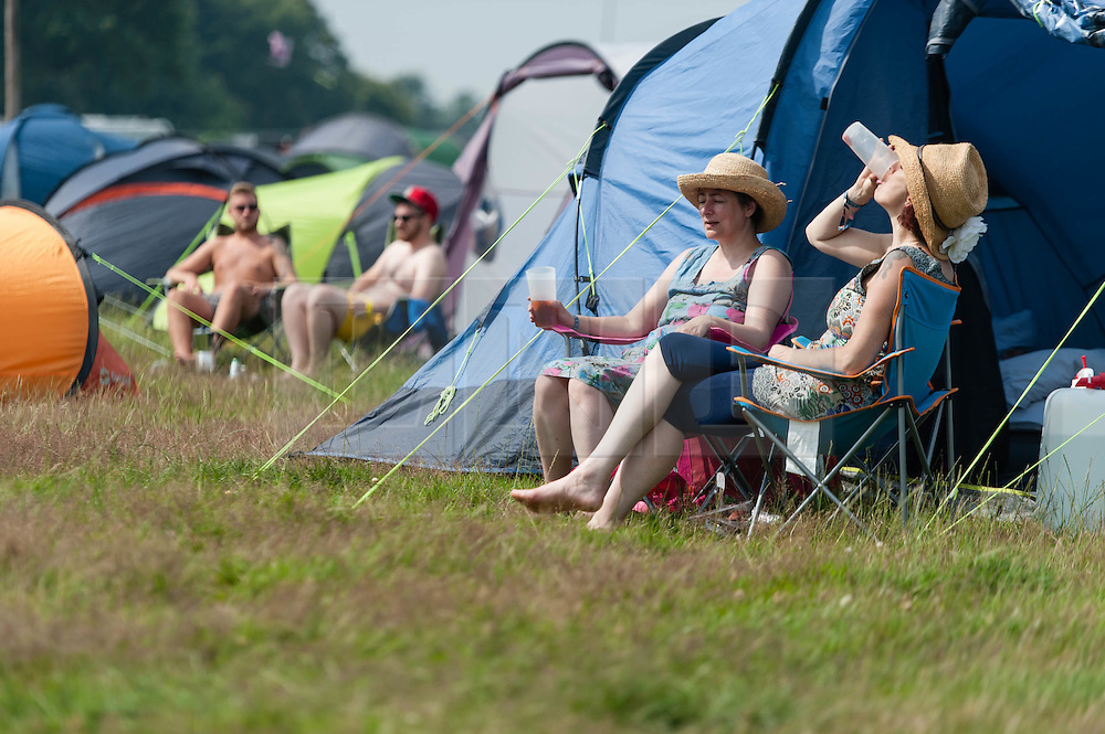 © Licensed to London News Pictures. 18/07/2014. Southwold, UK.   Festival goers sunbathe in the hot sun next to their tents at  Latitude Festival 2014 Day 1. Today is expected to be the hottest day of the year with temperatures forecast to reach 32 degrees centigrade.   Latitude is an British annual music festival.  Photo credit : Richard Isaac/LNP