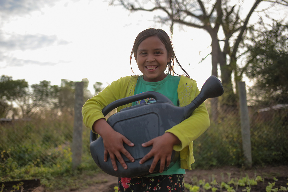 Mercedes Benitez, 10, of the Sanapaná indigenous community in Laguna Pato, Gran Chaco, Paraguay, with a watering can in her local community vegetable garden.<br /> <br /> Until recently, the Sanapaná people survived entirely as nomadic hunter, fisher gatherers. But as commercial farming has encroached dramatically on their traditional lands, they are now living in a reduced area of land, very small by Paraguayan farming standards, unable to move as they did between hunting and fishing grounds, and according to seasons for gathering in the forests. They are finding it hard adapting to the changes. While they still survive mainly by hunting and fishing, their diet, nutrition and food security has suffered. They live in very remote areas, and buying food is from travelling salesmen called 'macateros' is difficult because they are so overpriced and their incomes, from occasional labour on nearby farms, are so low.<br /> <br /> Church World Service supports the community by teaching them to grow vegetables for themselves and providing the seeds for community vegetable gardens. Despite setbacks from floods and droughts, the projects have been taken up enthusiastically by the indigenous people.