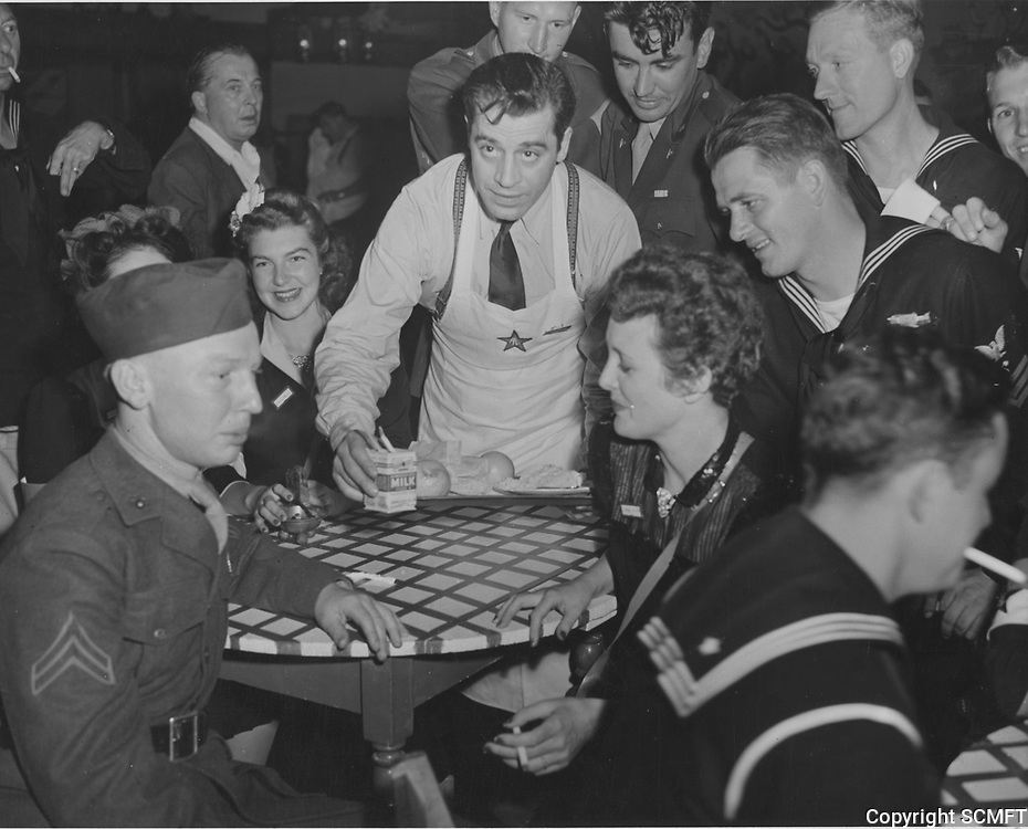 10/8/42 Actor, Jack LaRue serves milk to visiting servicemen and Mary Astor at the Hollywood Canteen