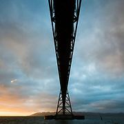 The Astoria-Megler Bridge is silhouetted during sunset in Astoria, Oregon.