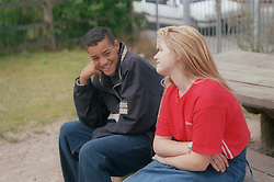 Teenage boy and girl sitting outdoors on park bench talking,