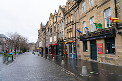 Edinburgh, Scotland, UK. 26 December 2020. Scenes from Edinburgh City Centre on a wet and windy Boxing Day during storm Bella. Today is first day that Scotland is under level 4 lockdown and all non essential shops and businesses are closed. As a result the streets are almost deserted with very few people venturing outside. Pic; Bars and restaurants all closed on The Grassmarket in the Old town.   Iain Masterton/Alamy Live News