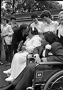 Historic Wedding Bells For Disabled Couple,  (N81)..1981..20.06.1981..06.20.1981..20th June 1981..Happy wedding bells chimed today for the first disabled couple in residential care to marry in the Republic of Ireland. The happy couple are Marie Skully and Pat Linehan and they were married in a special ceremony in The Cara Cheshire Home in the Phoenix Park. Both Marie and Pat are confined to wheelchairs because of their disabilities. After honeymoon, they will make their home in specially adapted quarters within the Cheshire residence...The Minister for Health, Dr Michael Woods, steals a kiss from the new Mrs Linehan.