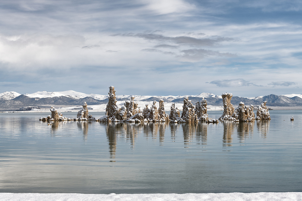 Tufa towers in Mono Lake are covered with a fresh layer of snow. Snow covered mountains and a volcanic crater rest in the background.
