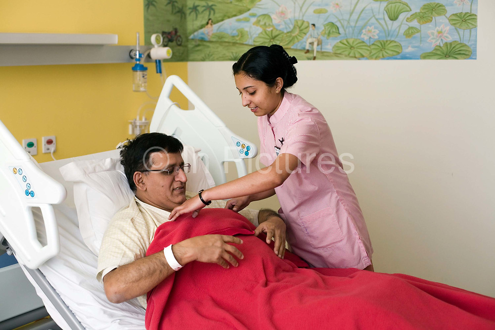 A nurse makes a patient comfortable in bed at the Medicity Hospital, Gurgaon<br /> <br /> The Medicity, Gurgaon is India's most technologically advanced multi disciplinary hospital. Founded by India's leading cardiac surgeon, Dr Naresh Trehan, it will when completed also contain a medical school and 1600 beds with over 48 operating theatres.