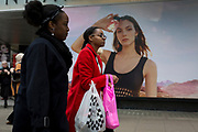 A lady shopper walks past a billboard ad featuring the face of a model advertising a perfume outside the retailer Debenhams on Oxford Street, on 16th April 2018, in London, England.