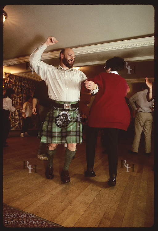 Jim and Liz Houston swing around, arm in arm, at ceilidh dance @ Black Bull Hotel; (v) Milngavie. Scotland