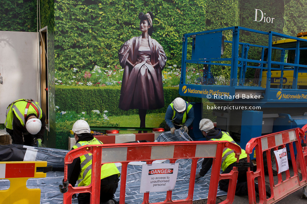 Workmen from Stewart Signs lay out temporary printed media to be hung outside a Dior shop being refurbished in central London.
