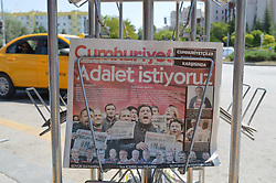 July 24, 2017 - Ankara, Turkey - A copy of Turkish opposition daily newspaper Cumhuriyet is seen at a kiosk as the newspaper depicts its first trial on the front page with a headline that reads 'We want justice' in Turkish in Ankara, Turkey on July 24, 2017. Seventeen directors and journalists from the newspaper go on the first trial on July 24, after spending over eight months behind bars. (Credit Image: © Altan Gocher/NurPhoto via ZUMA Press)