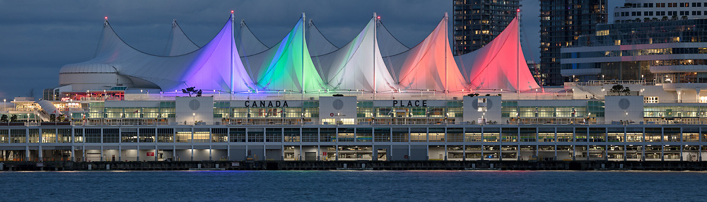 Decorative lights colour the sails on Canada Place in Vancouver, British Columbia, Canada. Located on the edge of Coal Harbour, Canada Place serves as a cruise ship terminal, trade and convention center space, and was the Canada Pavilion during Expo 86.