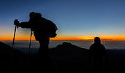 Climbers walk up the steep gravel and scree slope leading to the summit of Mount Kilimanjaro, one of the world's largest volcanoes and the highest free-standing mountain, shortly before sunrise in Tanzania January 4, 2006. The mountain has become an icon for environmental campaigners, with scientists predicting that the mountain's glaciers will vanish within the next twenty years because of global warming. Some 20,000 tourists attempt to climb to the summit every year. REUTERS/Darrin Zammit Lupi